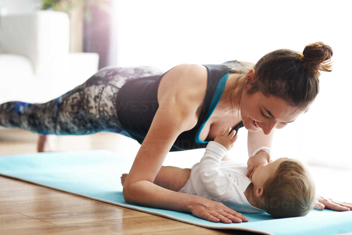 Mother with baby exercising on yoga mat at home - ABIF00337 - gpointstudio/Westend61