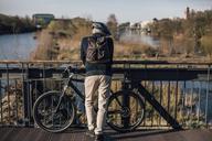 Cyclist standing on bridge - GUSF00640
