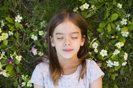 Portrait of girl lying on flower meadow, top view - LVF06870