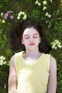Portrait of girl lying on flower meadow, top view - LVF06873
