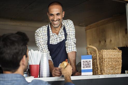 Smiling male vendor giving hotdog to customer at food truck - CAVF39481