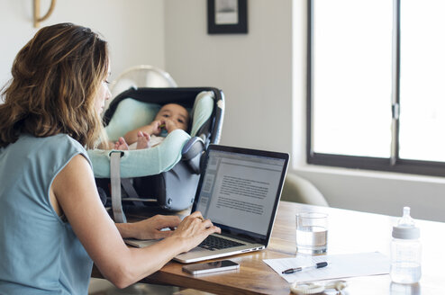 Mother using laptop computer by baby boy relaxing in seat on table at home - CAVF39505