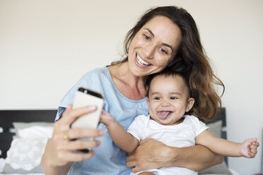 Happy mother taking selfie while sitting with son on bed at home - CAVF39523