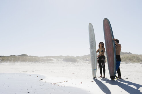 Friends with surfboards standing at beach against clear sky during sunny day - CAVF39559