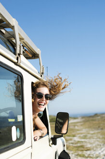 Happy woman in sunglasses peeking through car window during sunny day - CAVF39568