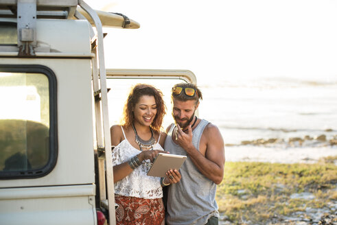 Woman showing tablet computer to boyfriend while standing by off-road vehicle at beach - CAVF39595