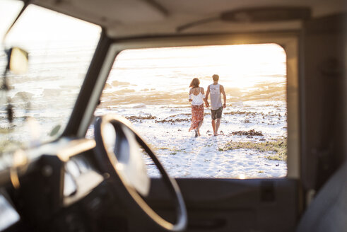 Rear view of couple walking at beach seen through off-road vehicle window - CAVF39598