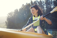 Happy woman kayaking on lake against sky during sunny day - CAVF39628