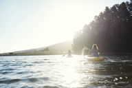 Rear view of friends kayaking on lake clear sky during sunny day - CAVF39634