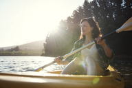 Smiling woman looking away while kayaking on lake during sunny day - CAVF39637