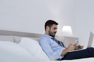 Side view of businessman using smart phone and laptop while sitting on bed in hotel room - CAVF39736