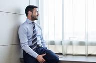 Thoughtful businessman looking through window in hotel room - CAVF39745