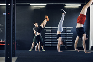 Trainer assisting athlete in doing handstand at gym - CAVF39763