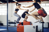 Athletes box jumping in gym - CAVF39769