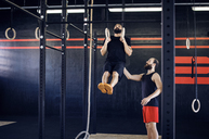 Trainer assisting athlete in exercising on gymnastic rings - CAVF39772
