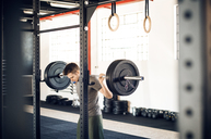 Man lifting barbell in health club - CAVF39781