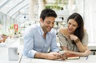 Smiling couple using smart phone at sidewalk cafe - CAVF39787