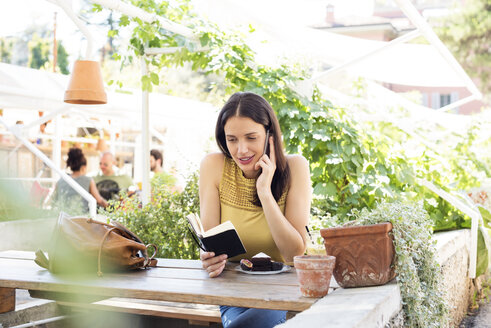 Woman reading diary while using smart phone at sidewalk cafe - CAVF39796