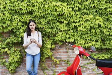 Portrait of woman holding smart phone while standing by motor scooter against ivy wall - CAVF39817