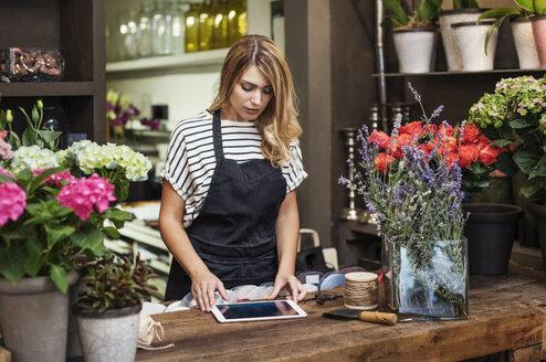 Owner using tablet computer in flower shop - CAVF39844