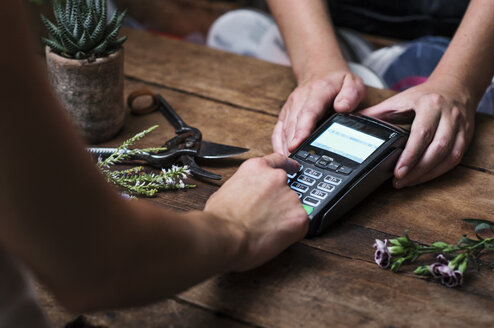 Cropped image of customer paying with credit card in flower shop - CAVF39850
