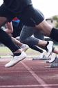 Athletes sprinting from starting blocks on track - CAVF39865