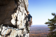 Side view of man rock climbing against clear sky - CAVF39919