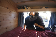 Rear view of couple kissing while sitting on bed in camper van - CAVF39925