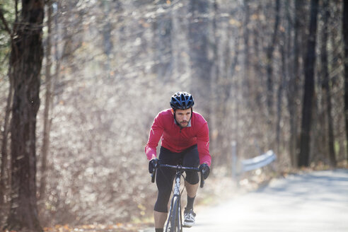 Male cyclist riding bicycle on road in forest - CAVF39952