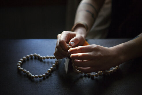 Cropped image of woman praying with beads in darkroom at home - CAVF39964