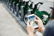 High angle view of woman using smart phone by bicycle rack on street - CAVF40021