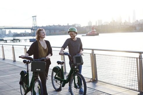 Smiling friends with bicycles walking on promenade by river - CAVF40039