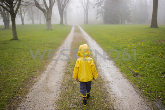 Rear view of boy in raincoat walking on dirt road during foggy weather - CAVF40060 - Cavan Images/Westend61