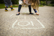 Girl playing hopscotch with brother on road - CAVF40066