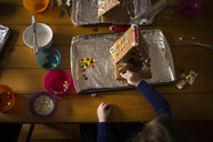 High angle view of girl decorating gingerbread house on table - CAVF40078