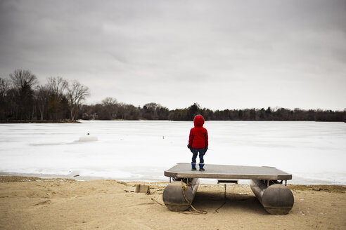 Rear view of boy standing on platform by frozen lake - CAVF40087