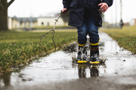 Low section of boy holding stick while jumping in puddle - CAVF40096