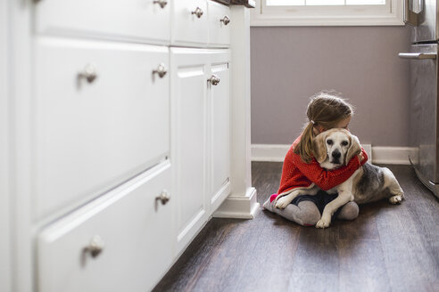 Girl embracing dog while sitting on floor at home - CAVF40099