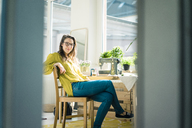 Portrait of fashion designer sitting at desk in her studio - MOEF01008
