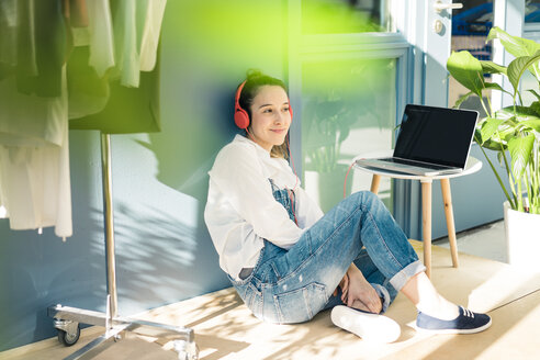 Smiling young freelancer sitting on the floor in her studio listening music with headphones and laptop - MOEF01017
