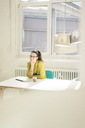 Portrait of happy freelancer sitting at desk in studio - MOEF01020