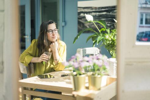Portrait of smiling fashion designer sitting at desk in her studio - MOEF01029