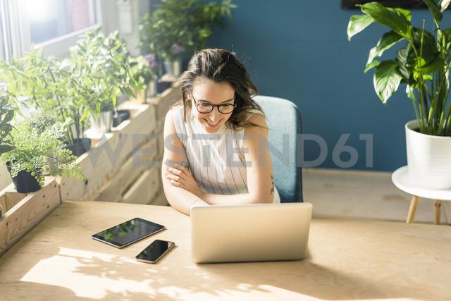 Smiling freelancer sitting at desk in loft looking at laptop - MOEF01032 - Robijn Page/Westend61