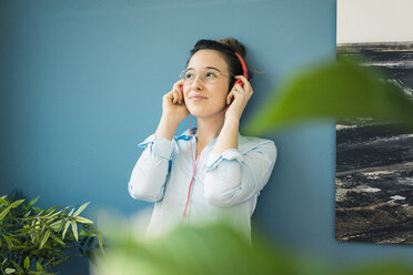 Portrait of smiling woman listening music with headphones - MOEF01035