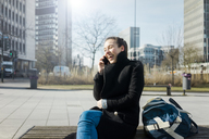 Germany, Essen, laughing young woman on the phone sitting on bench outdoors - MOEF01038