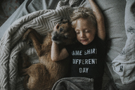 High angle view of boy sleeping with dog on bed at home - CAVF40132