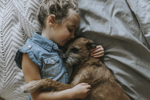 High angle view of girl sleeping with schnauzer on bed - CAVF40141