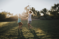 Happy siblings playing on grassy field in backyard - CAVF40150