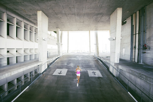 High angle view of sporty woman running in parking lot - CAVF40204
