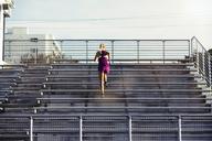 Rear view of female athlete running on bleachers at stadium - CAVF40210